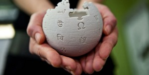 Hands are cupping a mini wikipedia globe made from wet sand