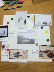 Board with counters in a circle and postcards of artic scenes including penguins, sleds, and seals