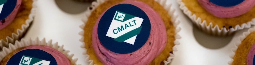 Round cupcakes with pink icing and the CMALT logo.