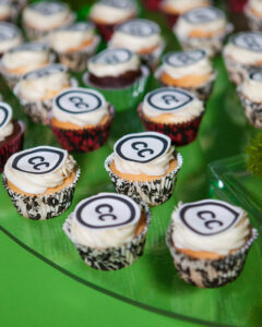 Photograph of cupcakes with white icing and the CC logo on top against a green background.