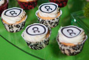 Cropped photograph of cupcakes with white icing and the CC logo on top against a green background.