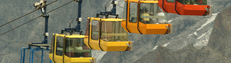 Four aerial tramway cars going up the side of a slightly snow covered mountain.
