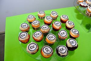 Picture of a circular glass pate on a green table. The plate is covered in multiple cupcakes, each cupcake has a decoration with the letters CC inside a black circle.