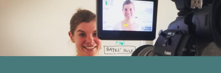 Woman standing in front of a whiteboard being recorded on a professional video camera