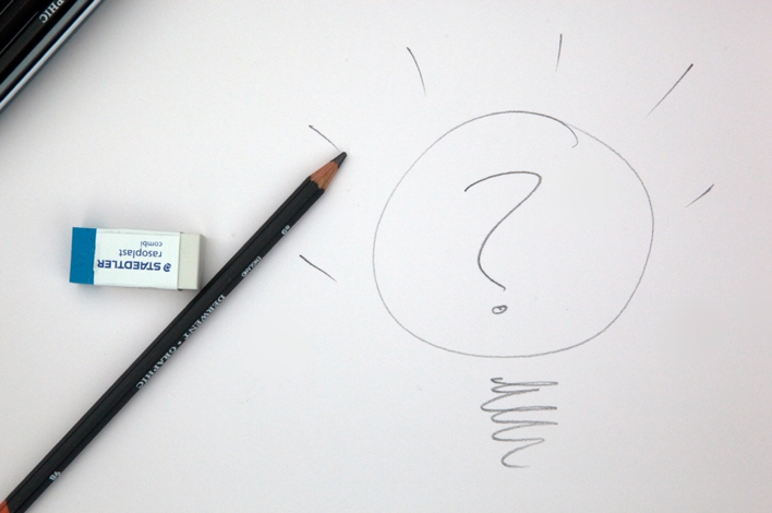 Photograph of a sketch of a question mark, alongside a pencil and an eraser