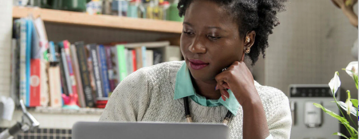 A professional black woman with natural hair is studying at a laptop
