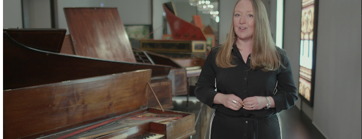 Dr Sarah Deters standing next to a piano