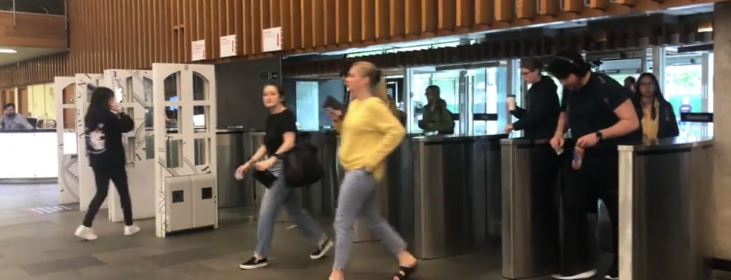 Students scanning their cards and walking into the library