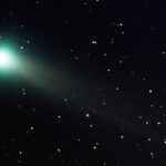 A photo of a comet with a green haze surrounding, with stars around