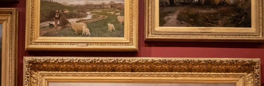 photo of an art gallery with several paintings of animals and nature that are ornate gold framed