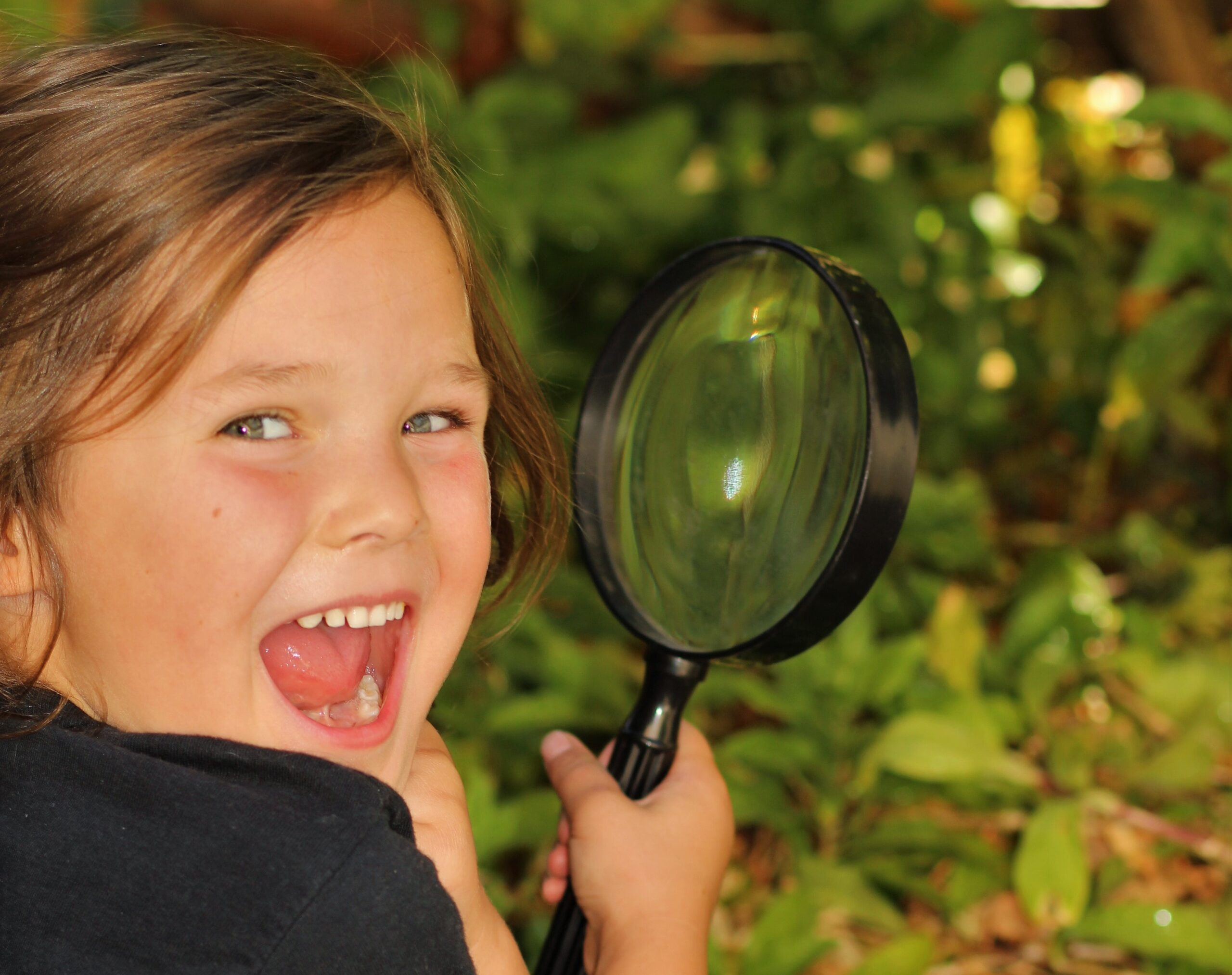 Photograph of a child with a magnifying glass