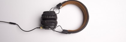 White background with a pair of brown over-ear full sized headphones
