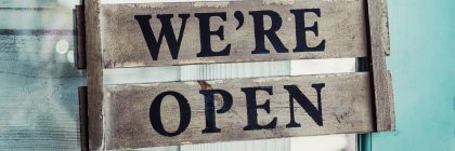 We're Open text painted on grey wood with blue background
