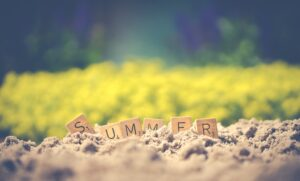 scrabble tiles spelling out Summer in the sand