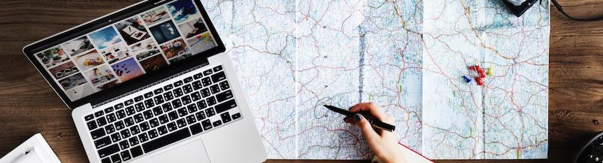 Laptop, map, and a hand holding a pen hovering over the map