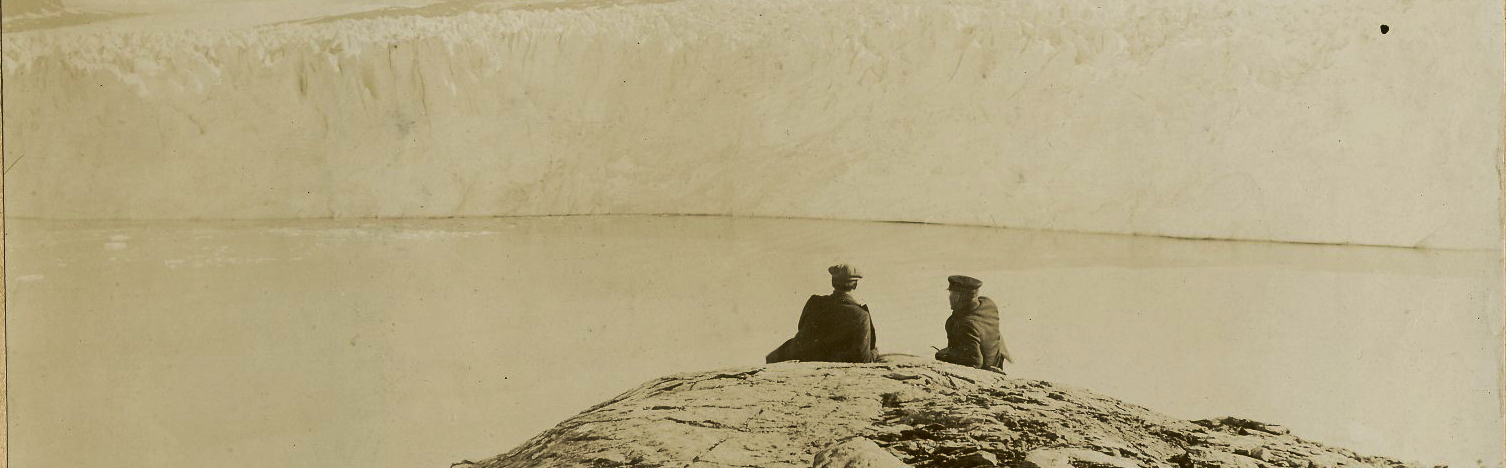 Two men sitting on a rocky cliff looking out across the water at a glacier