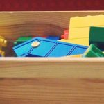 Wooden box with yellow, green, blue, and red duplo blocks.